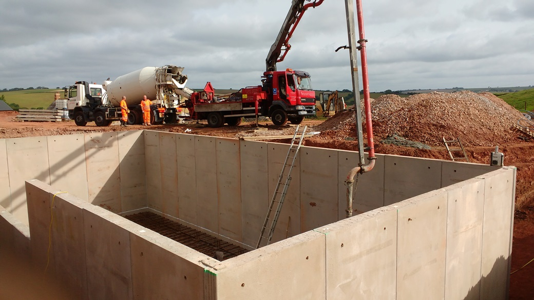 Laying concrete in pre-cast walled slurry tank